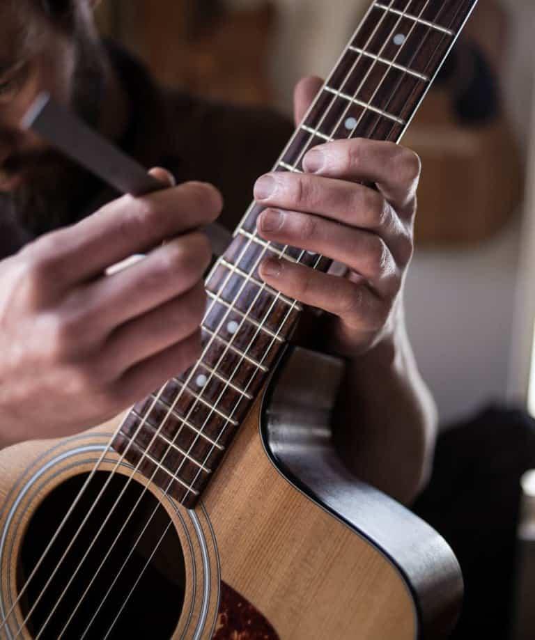 Guitar tech checking string height