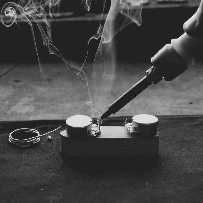 Guitar tech soldering a volume pot