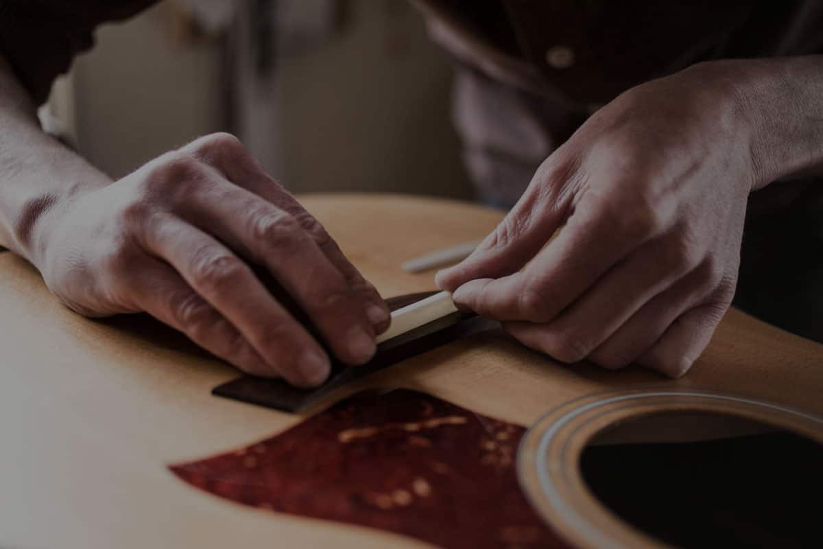 Repair tech setting a new saddle on an acoustic guitar
